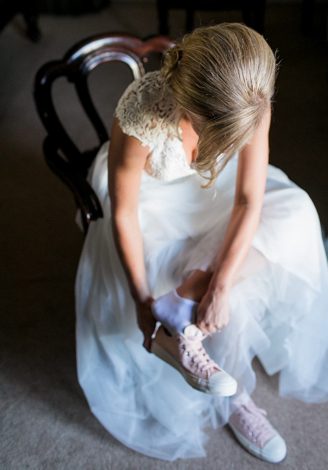 Bride putting on pink converse before ceremony