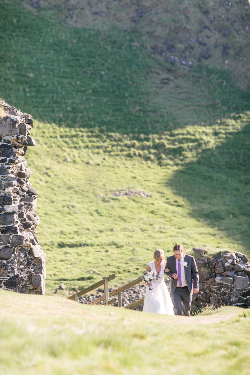bride going up the hill to begin the wedding ceremony in kinbane castle in northern ireland