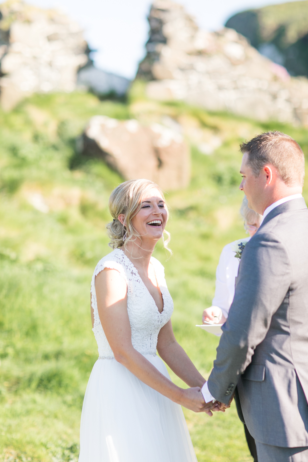 bride laughing during the outside ceremony in kinbane castle in northern ireland
