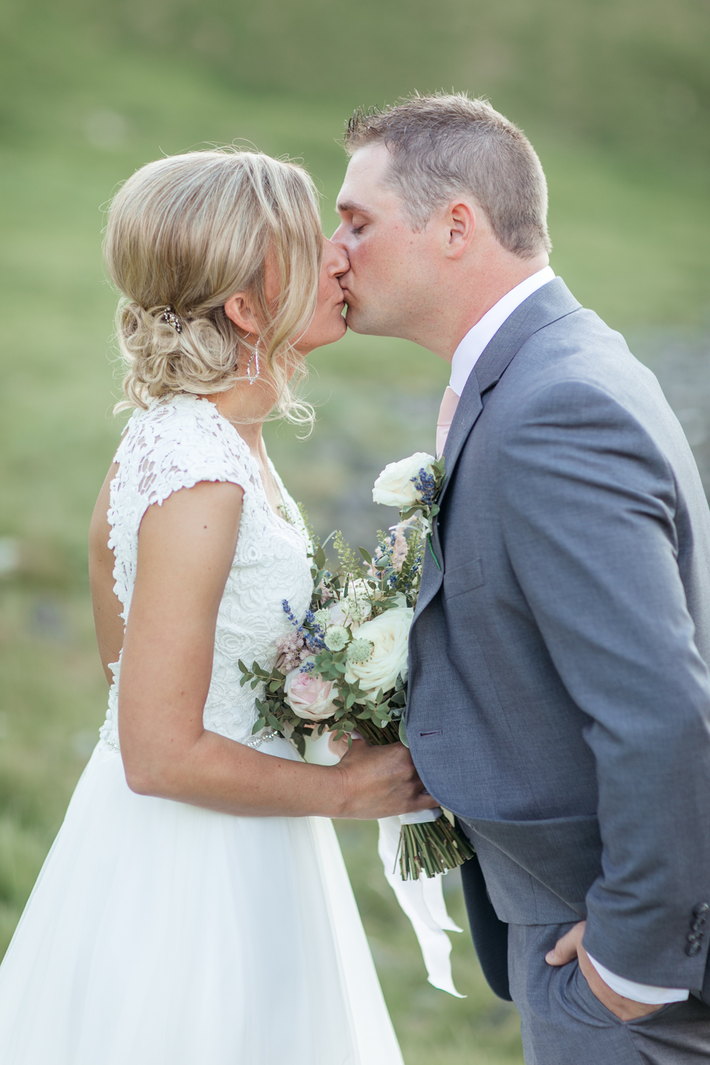 Bride and groom kissing after the ceremony in grey wedding suit and a lace wedding dress