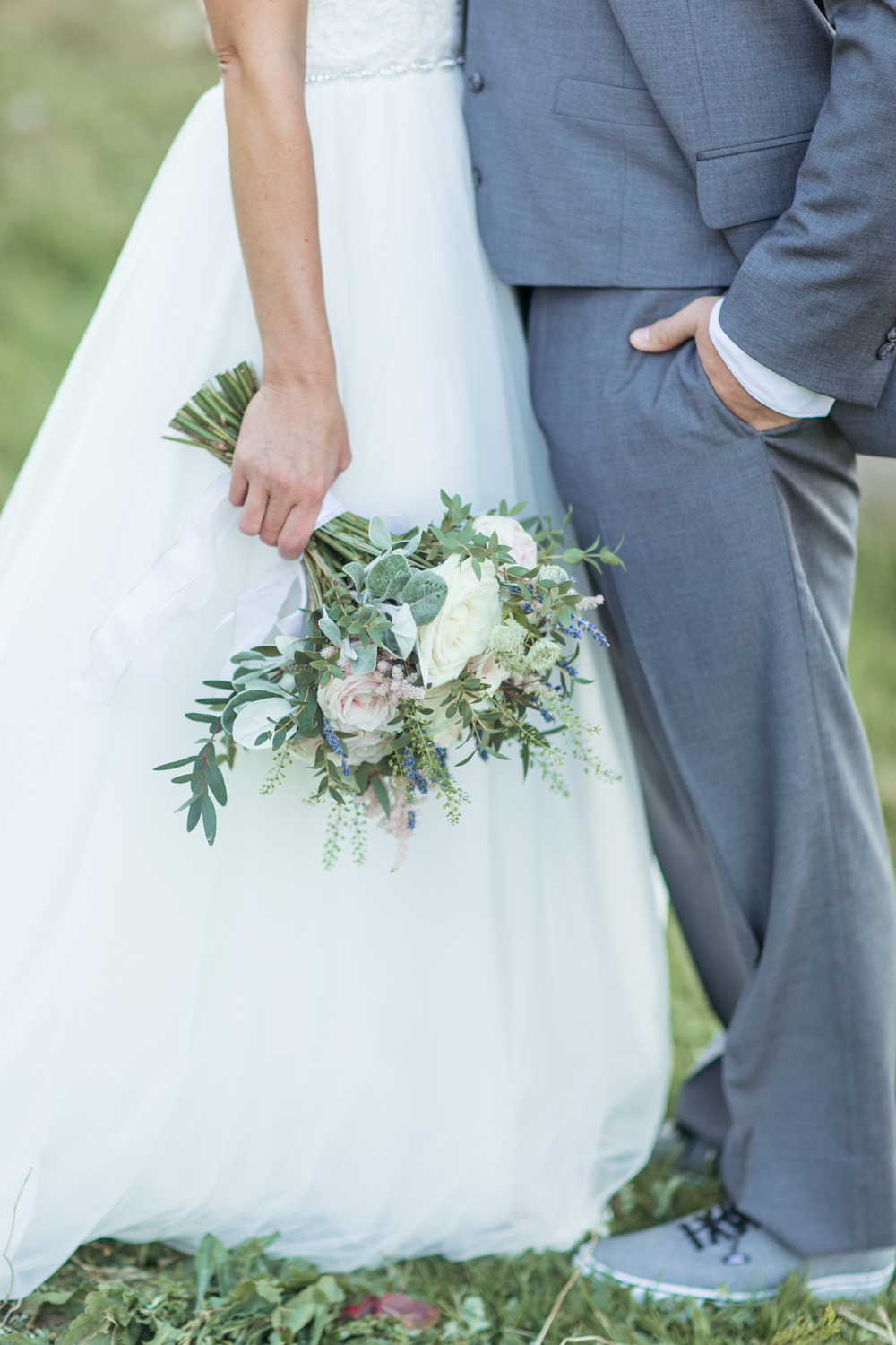 bride holding her loose bridal bouquet agains a tulle skirt of a wedding dress
