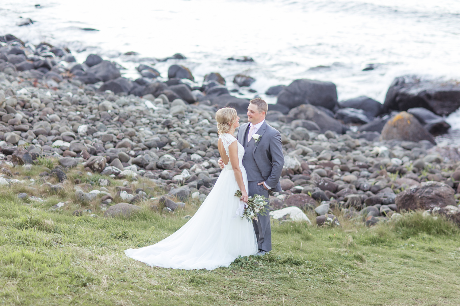 Bride and groom with the view of the atlantic ocean, rocky background in northern ireland after their elopement ceremony