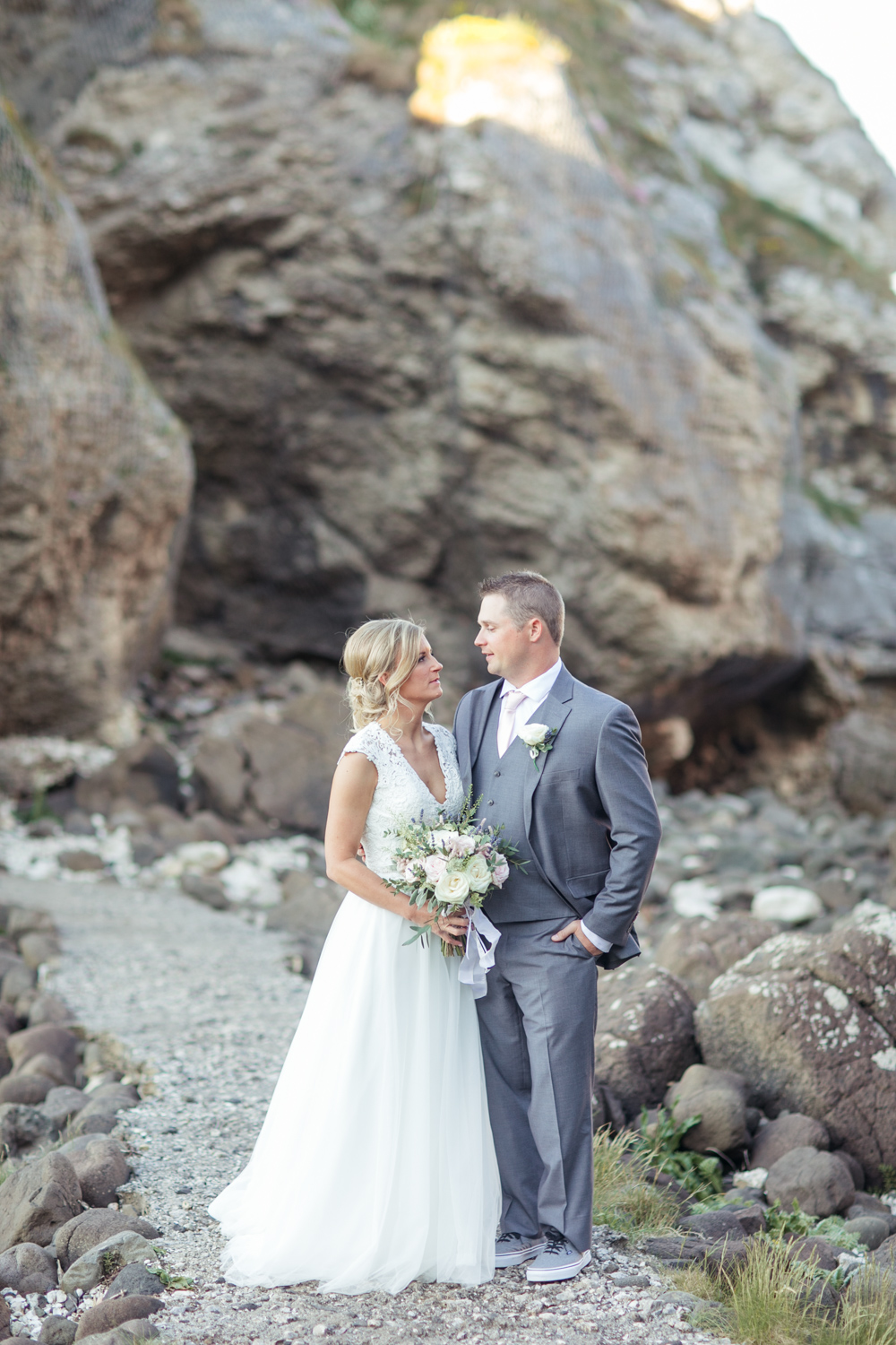 oceanic rocky background with bride and groom bride wearing modern loose dress