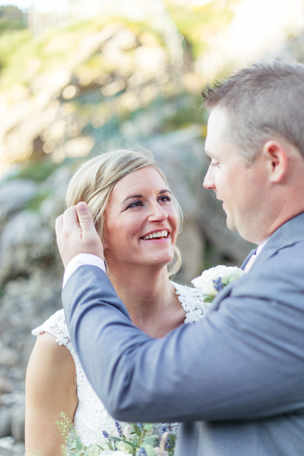 groom tenderly fixes the brides hair while she is smiling looking up at him