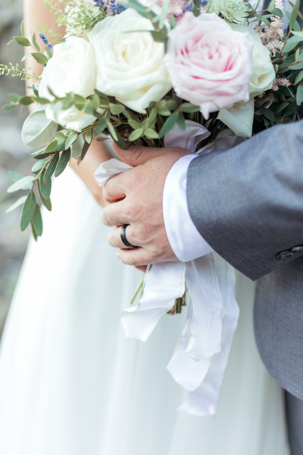 a close up of bride and groom holding the wedding flowers loose summery bouquet