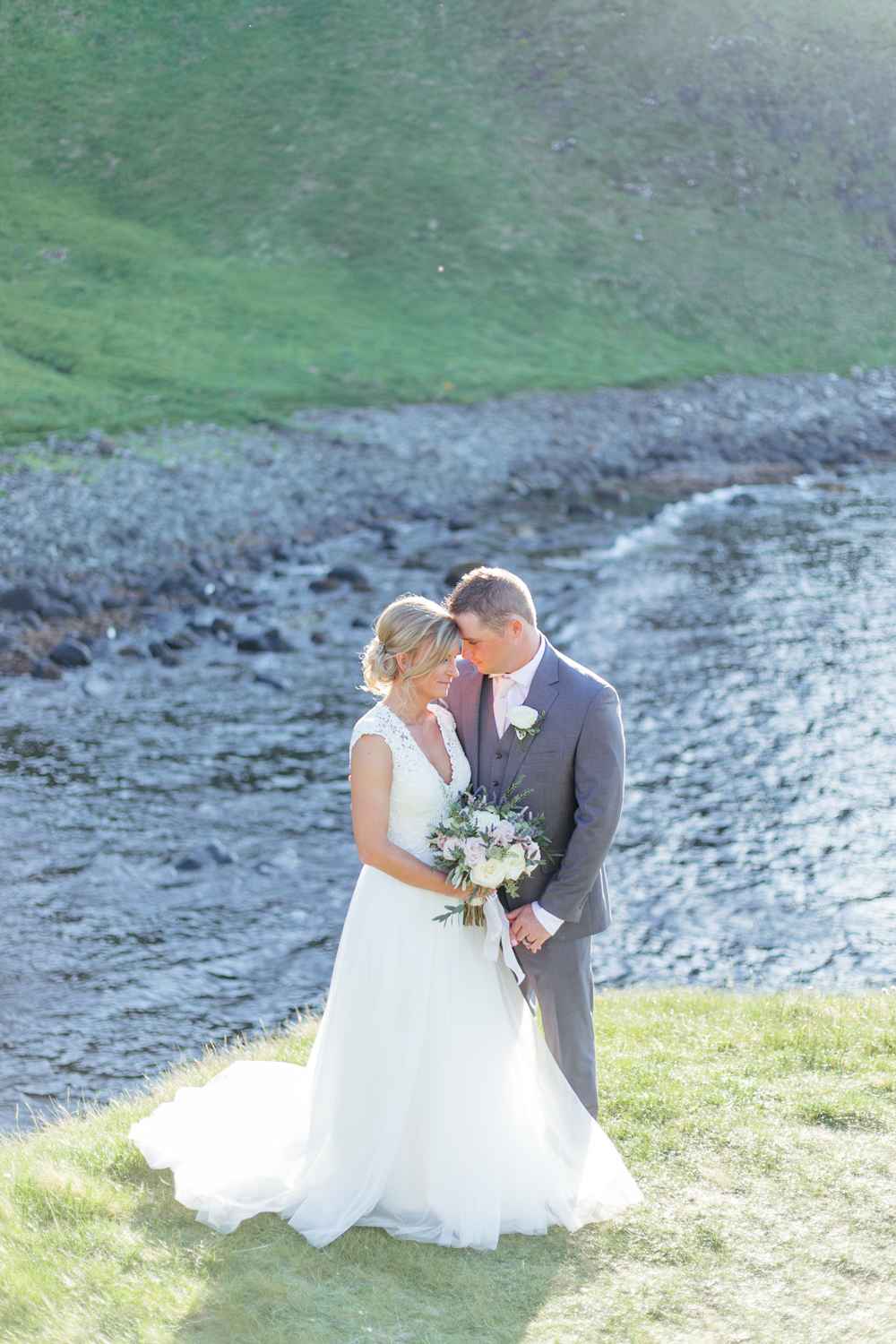 bride and groom standing on the hill top of kinbane castle close to eachother in the evening light