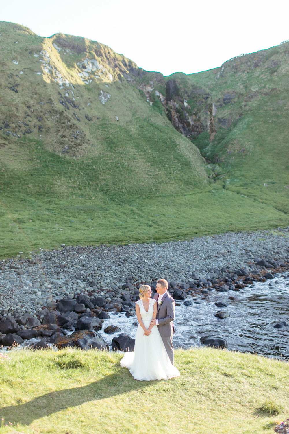 A beautiful image of a hill top bride and groom in the evening light of kinbane castle