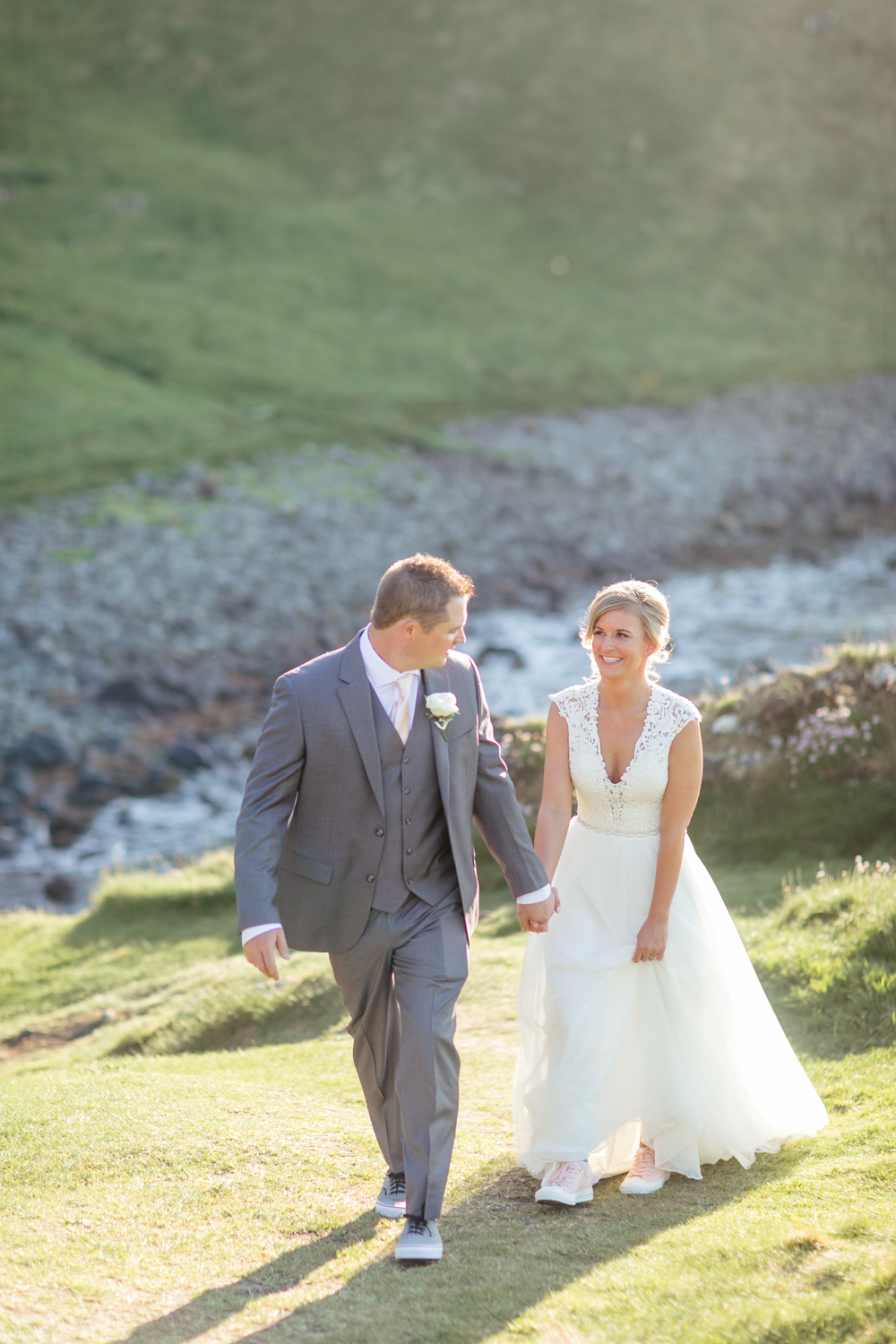 Bride and groom walking in the evening sunlight wearing converse shoes