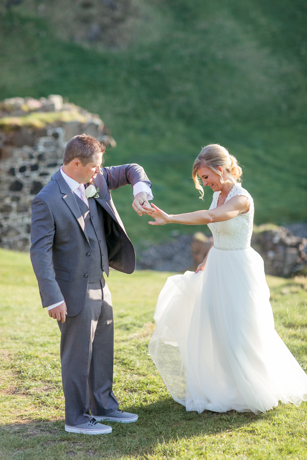 bride is twirling in front of the groom with the kinbane castle in the background