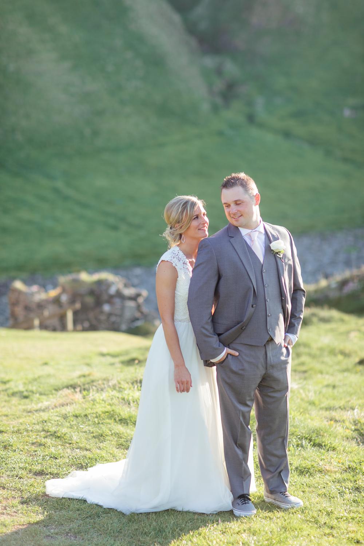 bride posing slightly behind the groom for their wedding photographs in kinbane castle in northern ireland
