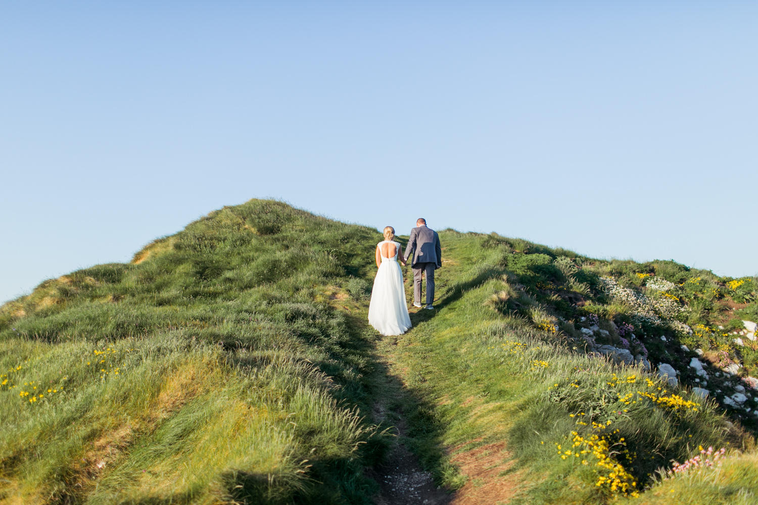 the back of the brides dress as bride and groom walk up a beautiful hill of kinbane castle in northern ireland