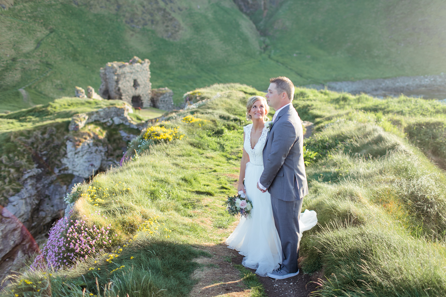a full view of kinbane castle in the background while bride and groom are posing for their elopement photographs