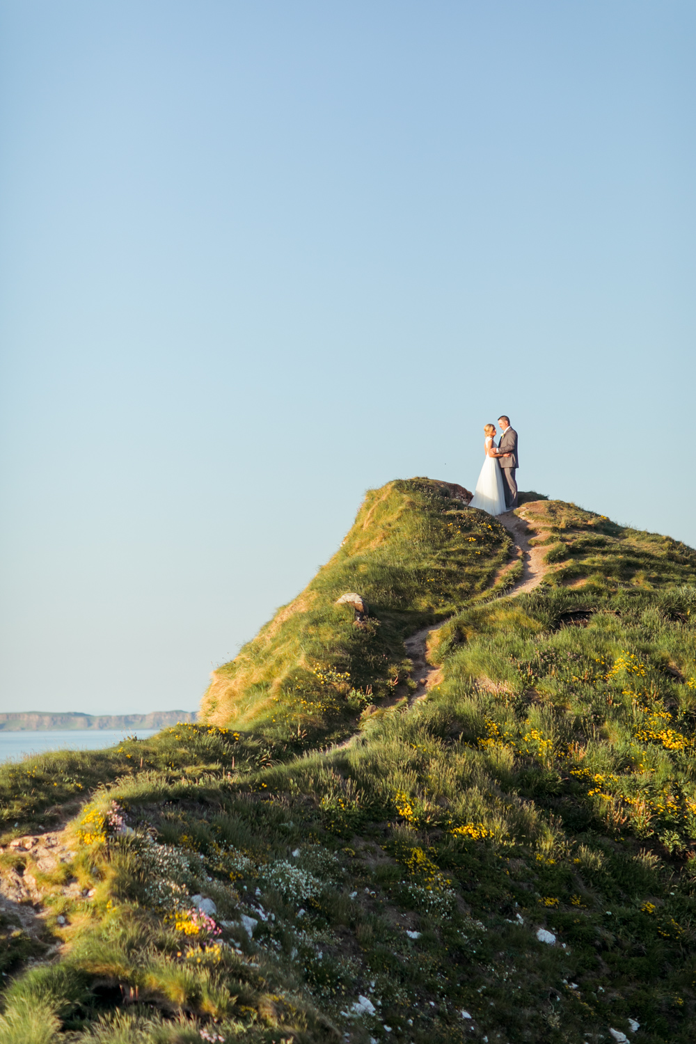 bride and groom on the very top of the kinbane castle hill with a leading path across the ocean