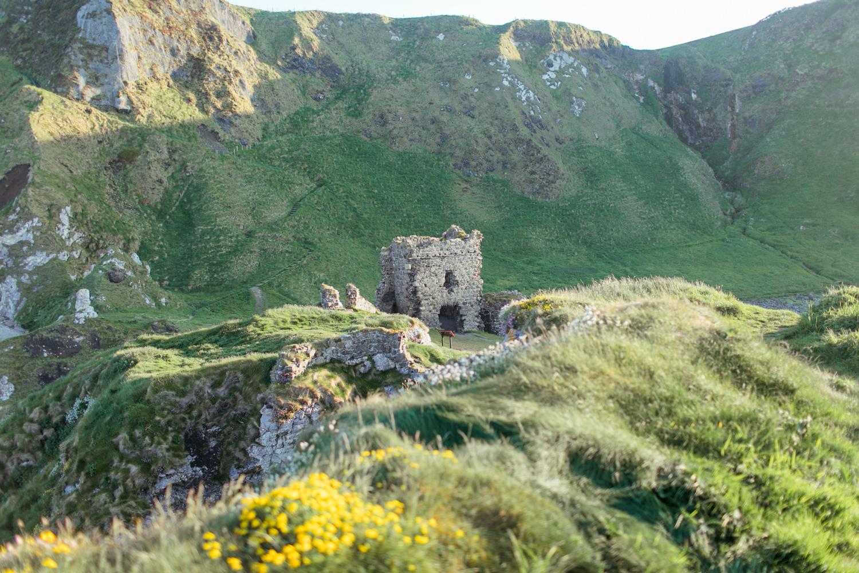 a photograph of the ruin of kinbane castle in the setting sun of the northern irish coastline