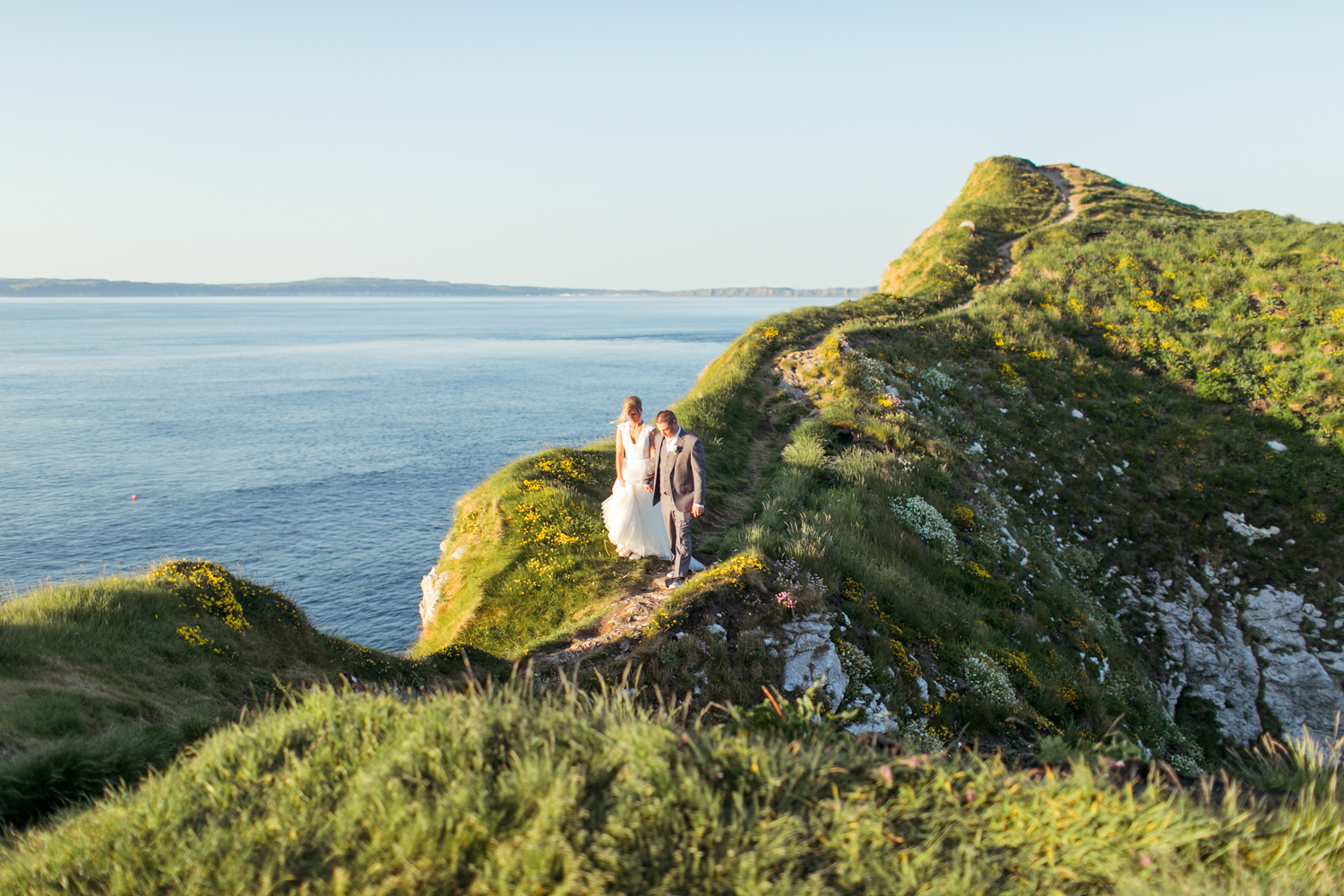 bride and groom crossing the naturally formed path with the ocean atlantic underneath