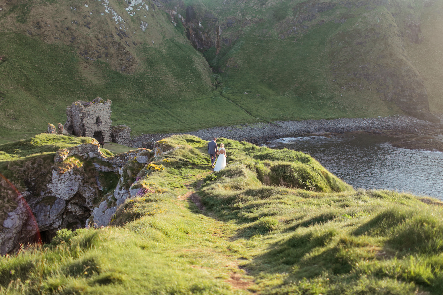 Bride and groom in the distance with the entire view of kinbane castle in the setting summer light