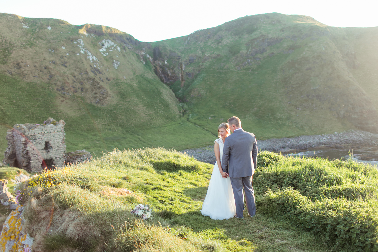 Bride and groom posing naturally with the view of kinbane castle in the background