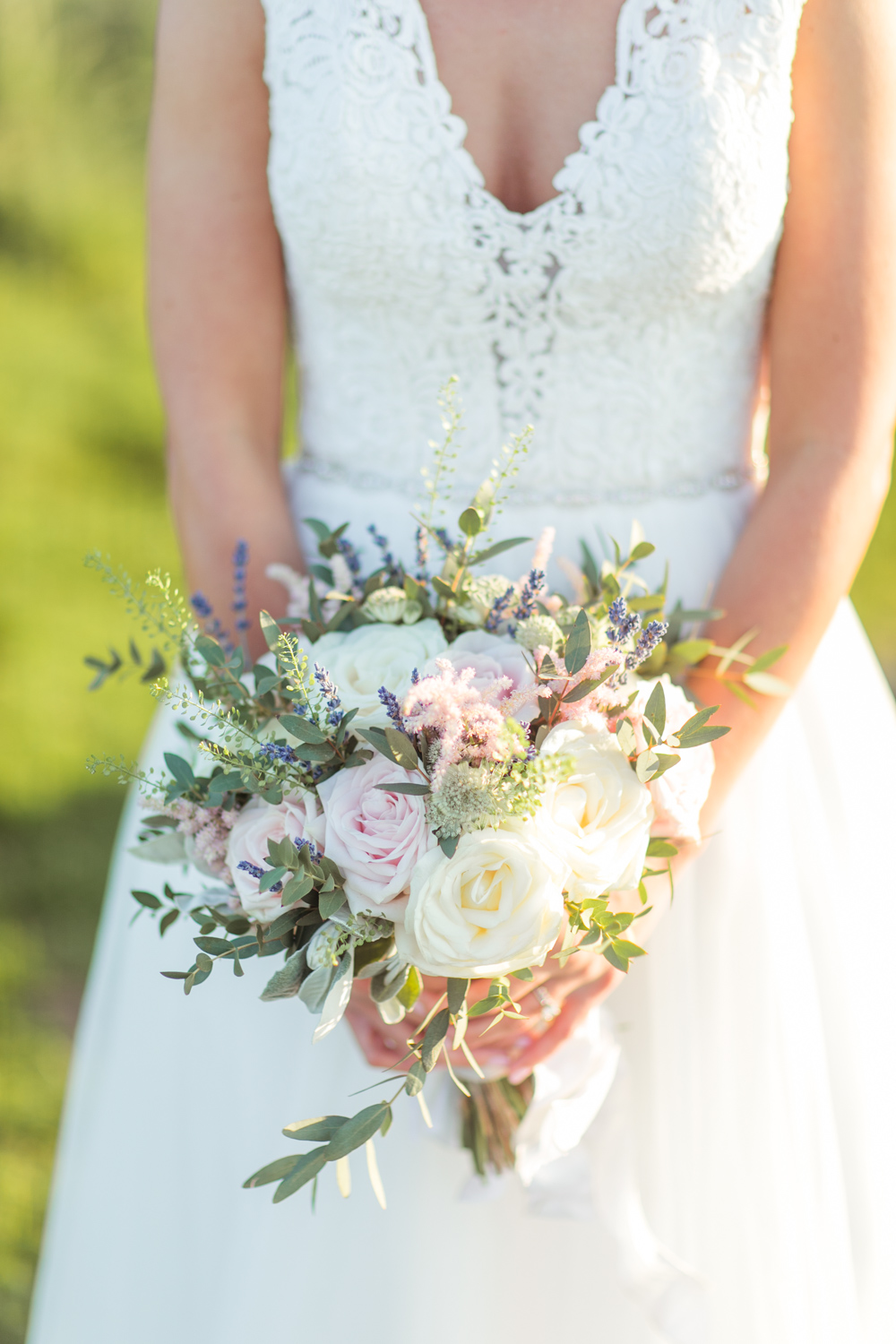 lace top wedding dress top with a deep plunge and pastelle loose wedding bouquet with wildflowers