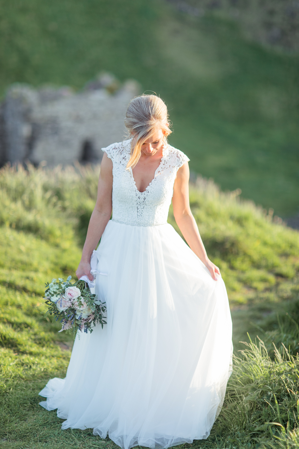Modern tulle dress with a lace top and a loose summer bouquet with fildflowers