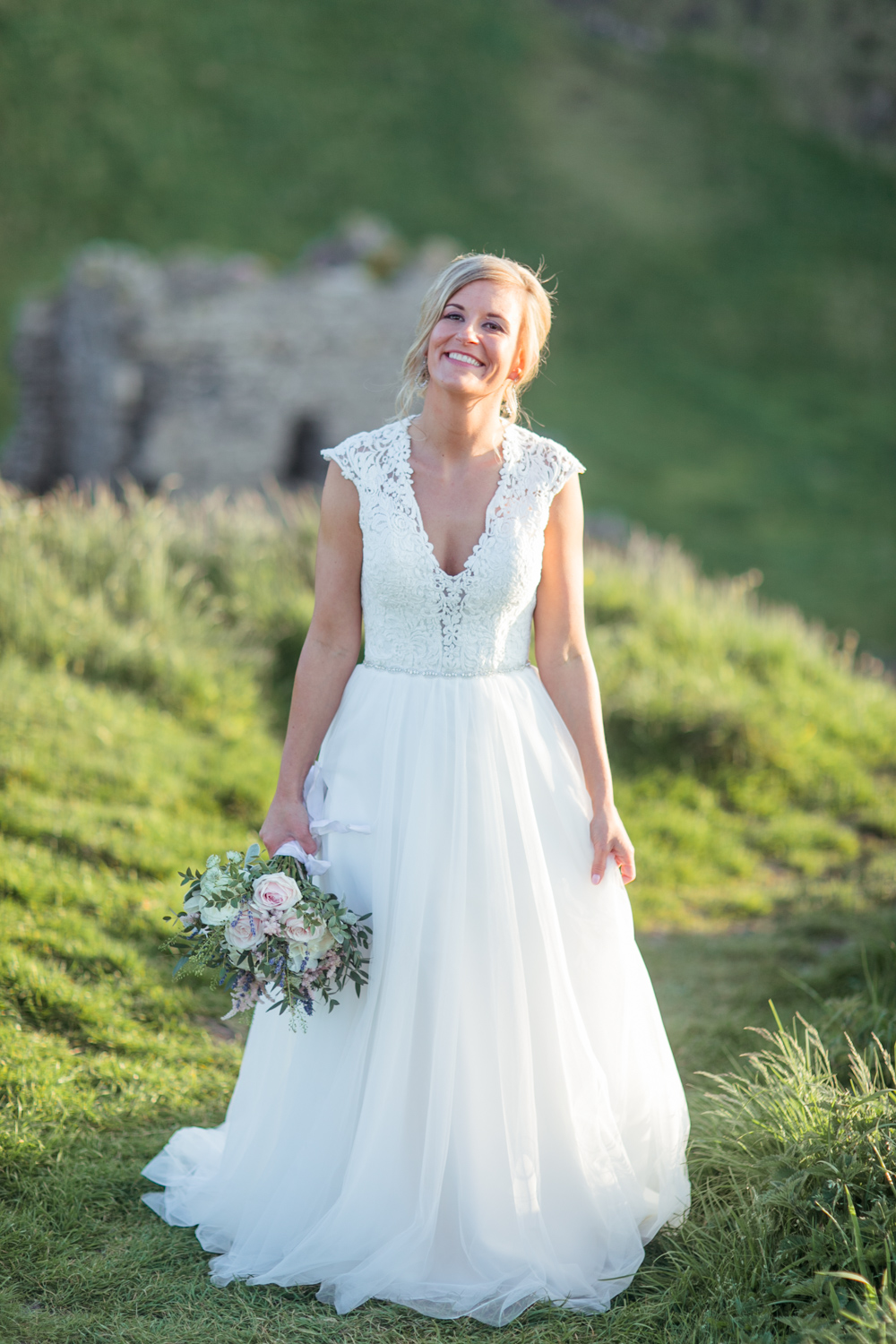 bride is smiling holding the tulle skirt of her wedding dress in one hand and loose flower bouquet in another hand