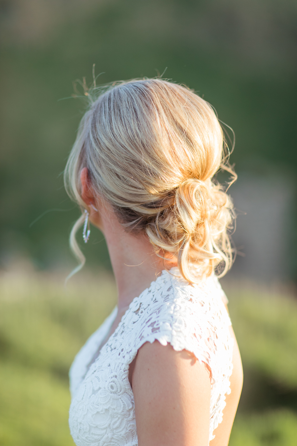 lace top of a wedding dress with shoulder caps and a loose upstyle hairdo