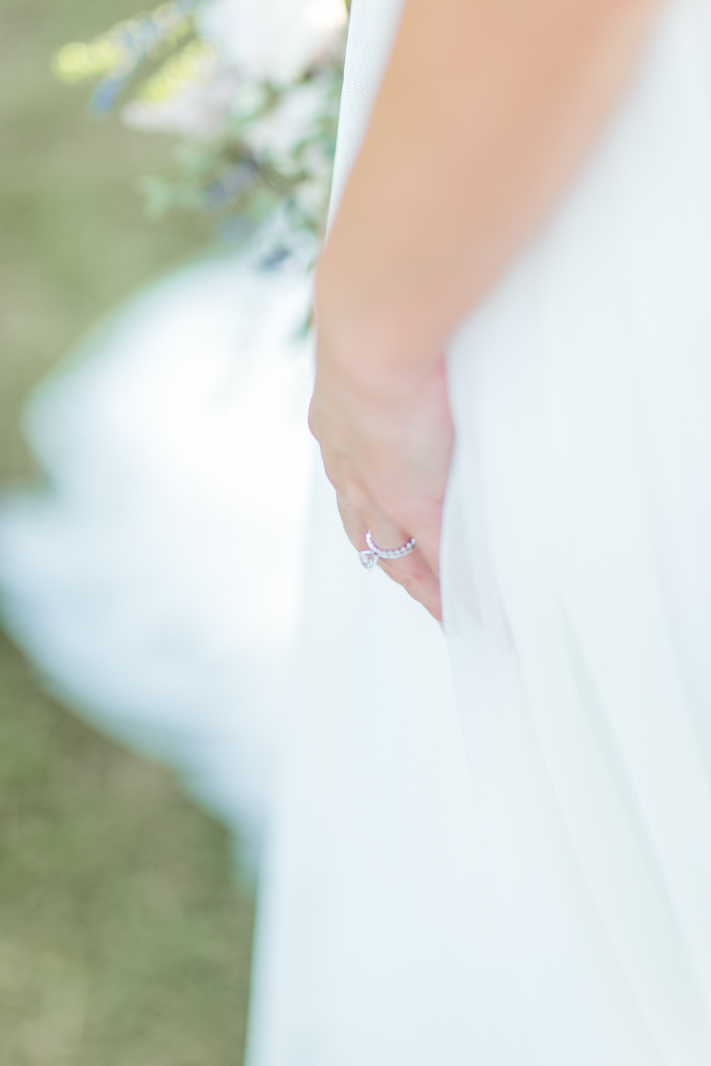 wedding ring in a tulle dress while the bride is holding the skirt