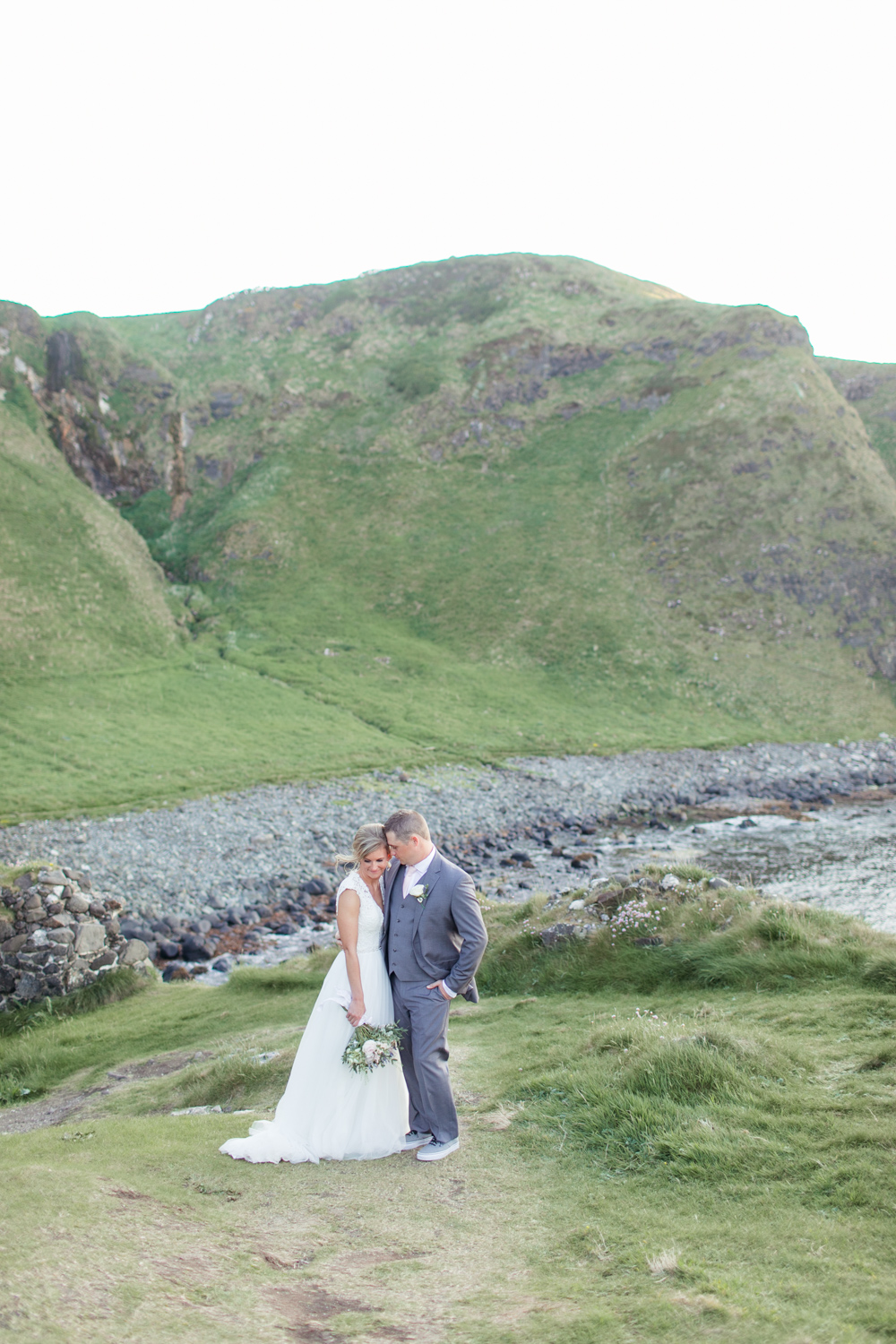 bride and groom with the rocky atlantic ocean background in northern ireland