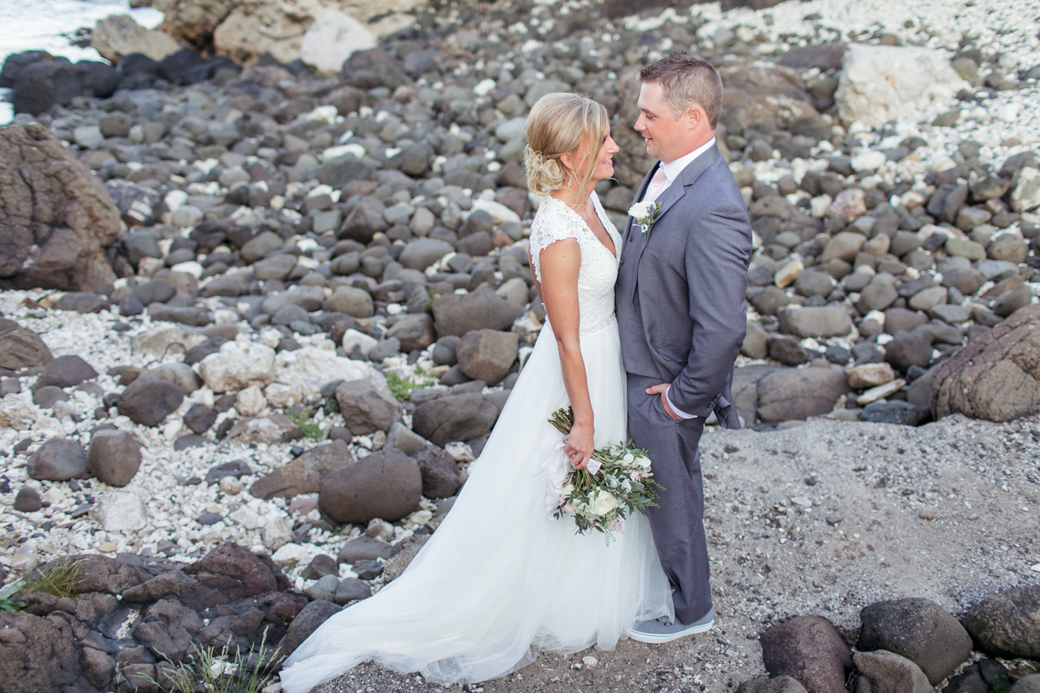 elopement photographs in kinbane castle of a bride and groom in a grey wedding suit and a wedding dress with tulle skirt