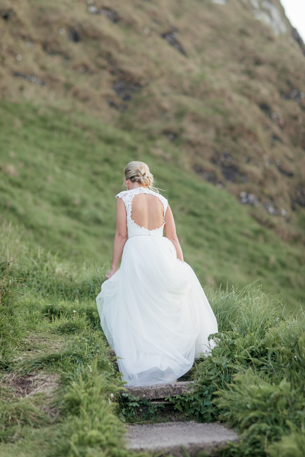 bride walking up the hill after a photoshoot with her open back dress and a tulle skirt