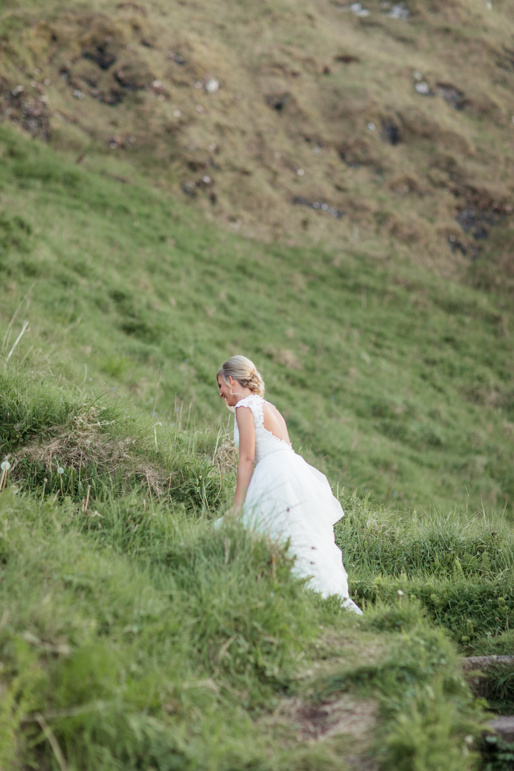 a moment when bride is walking up the hill after the elopement ceremony in kinbane castle