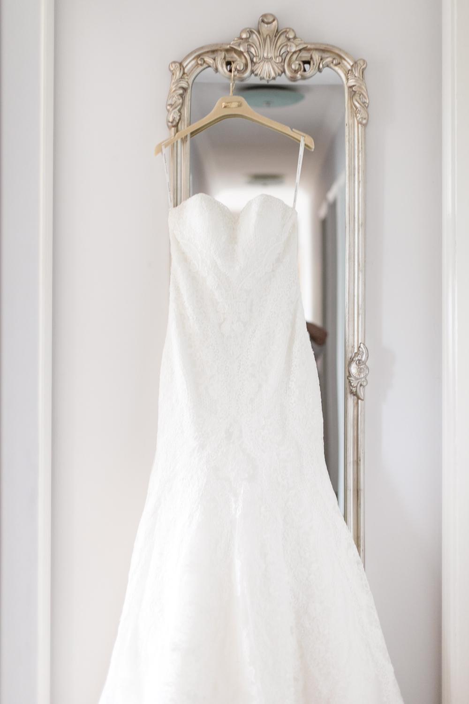 White wedding dress hanging on a vintage mirror