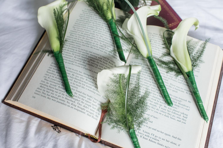 button hole white callas on a book for a wedding day