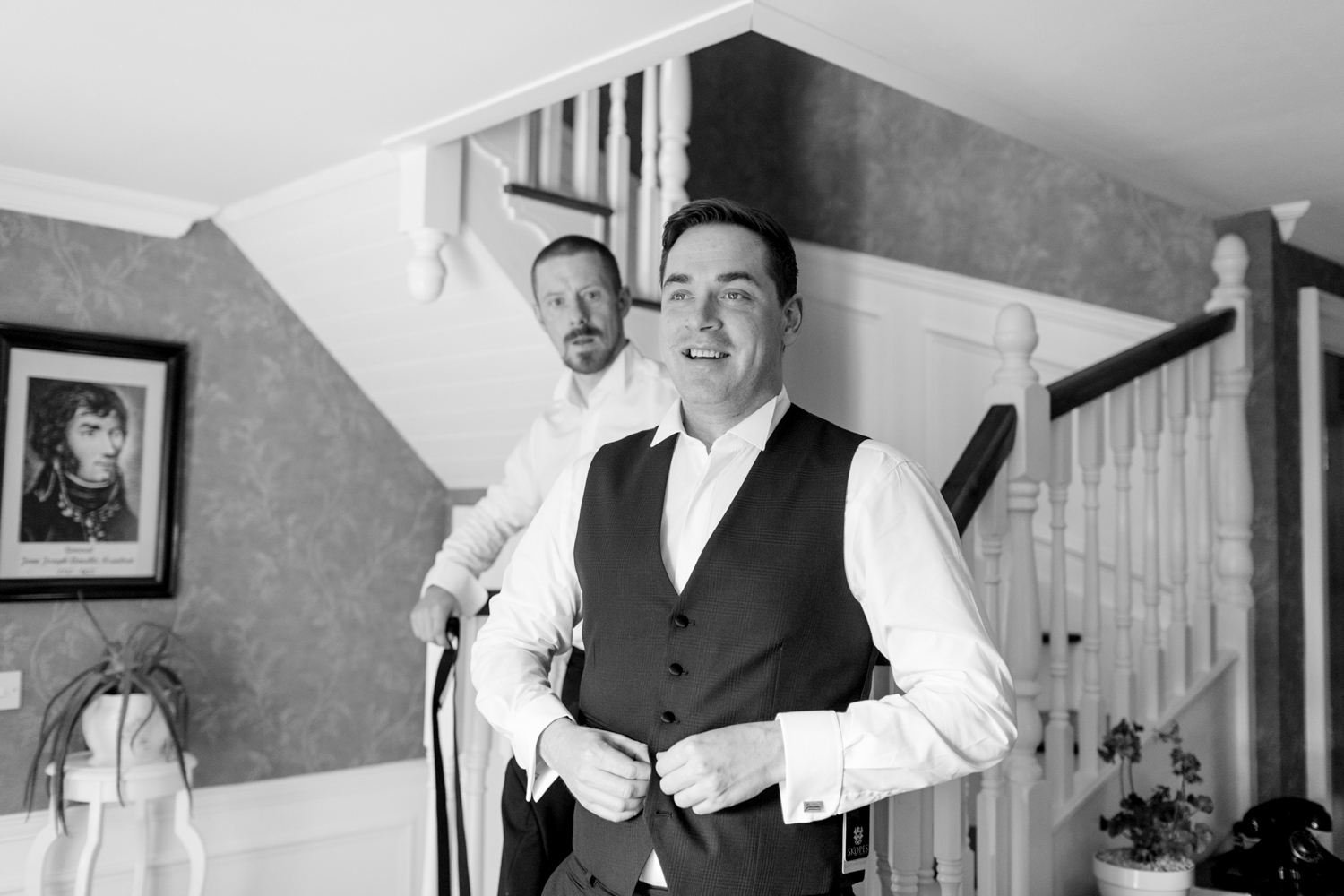 groom on the day of the wedding buttoning a vest for his black tie outfit