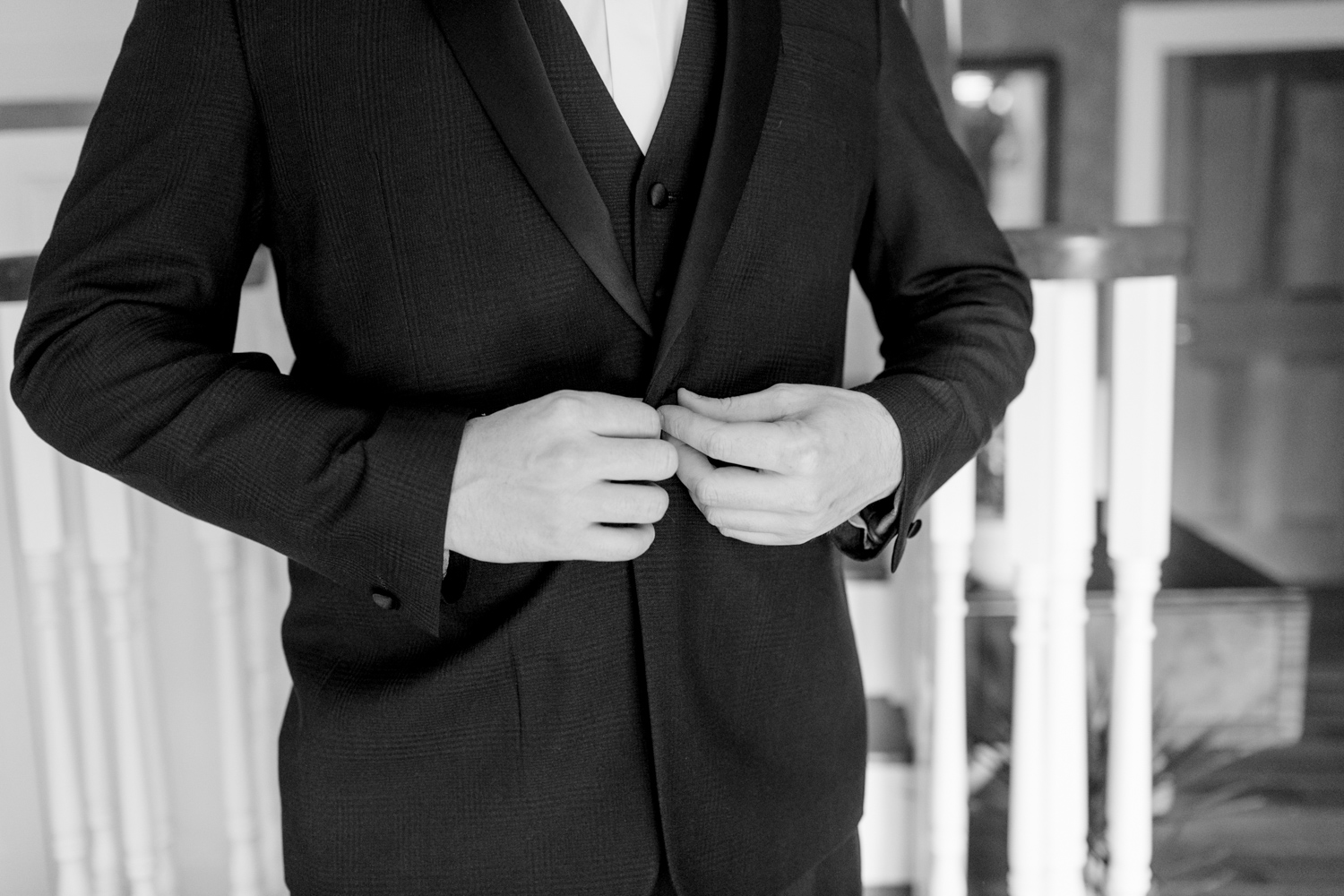 groom buttoning the jacket of his black tie tux