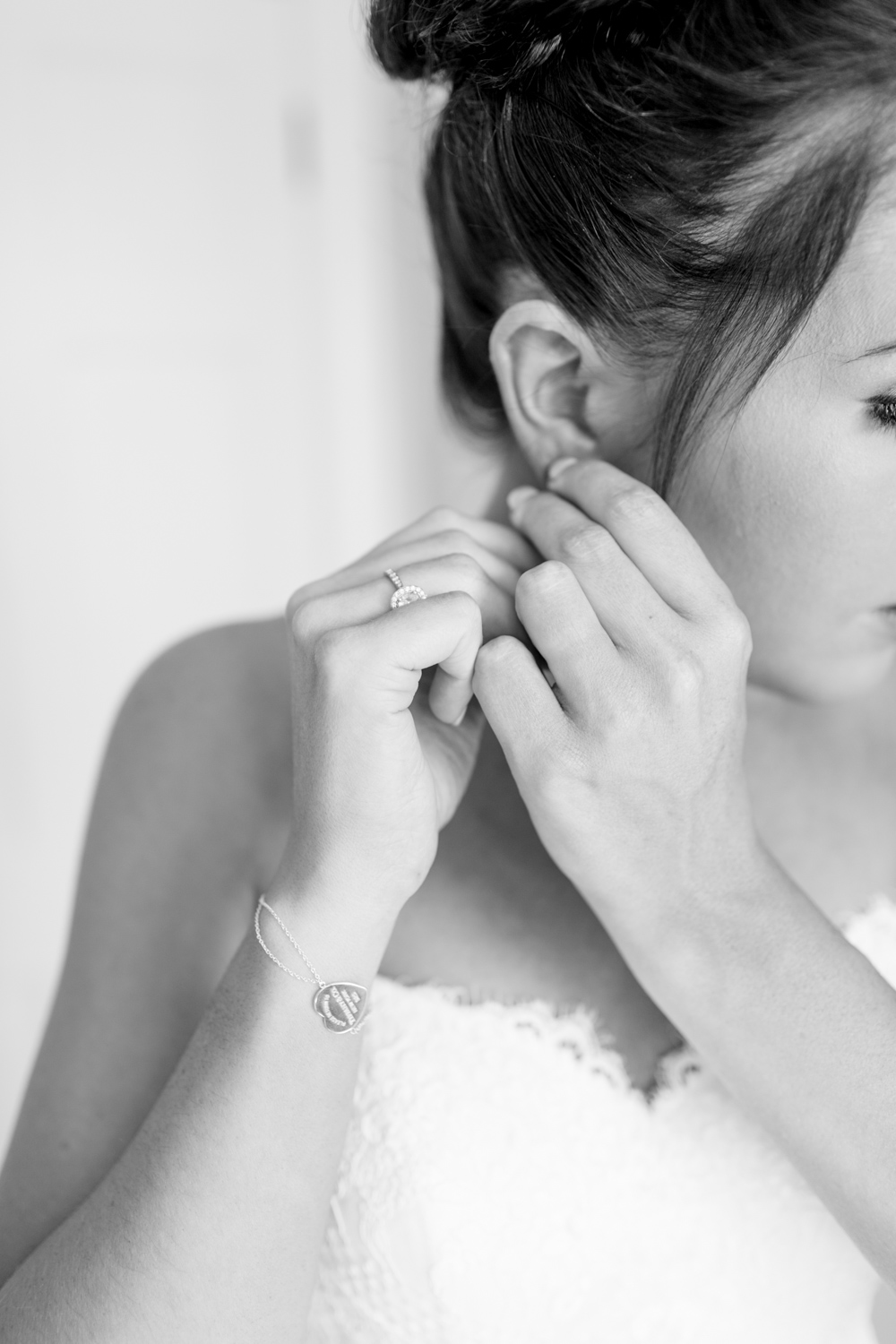 bride fastening the earring on the morning of her wedding day