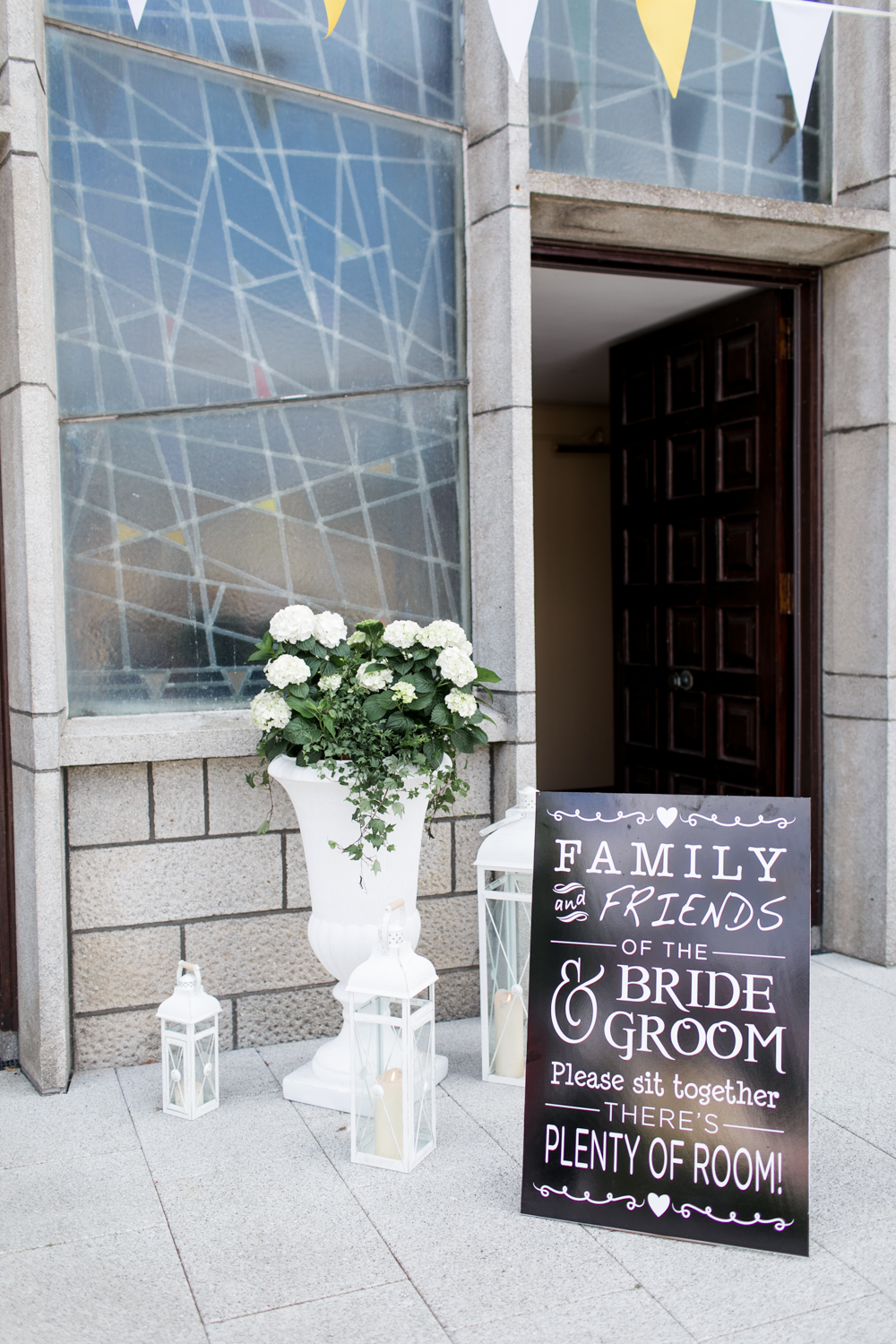 wedding ceremony sign outside the church with white roses and candles