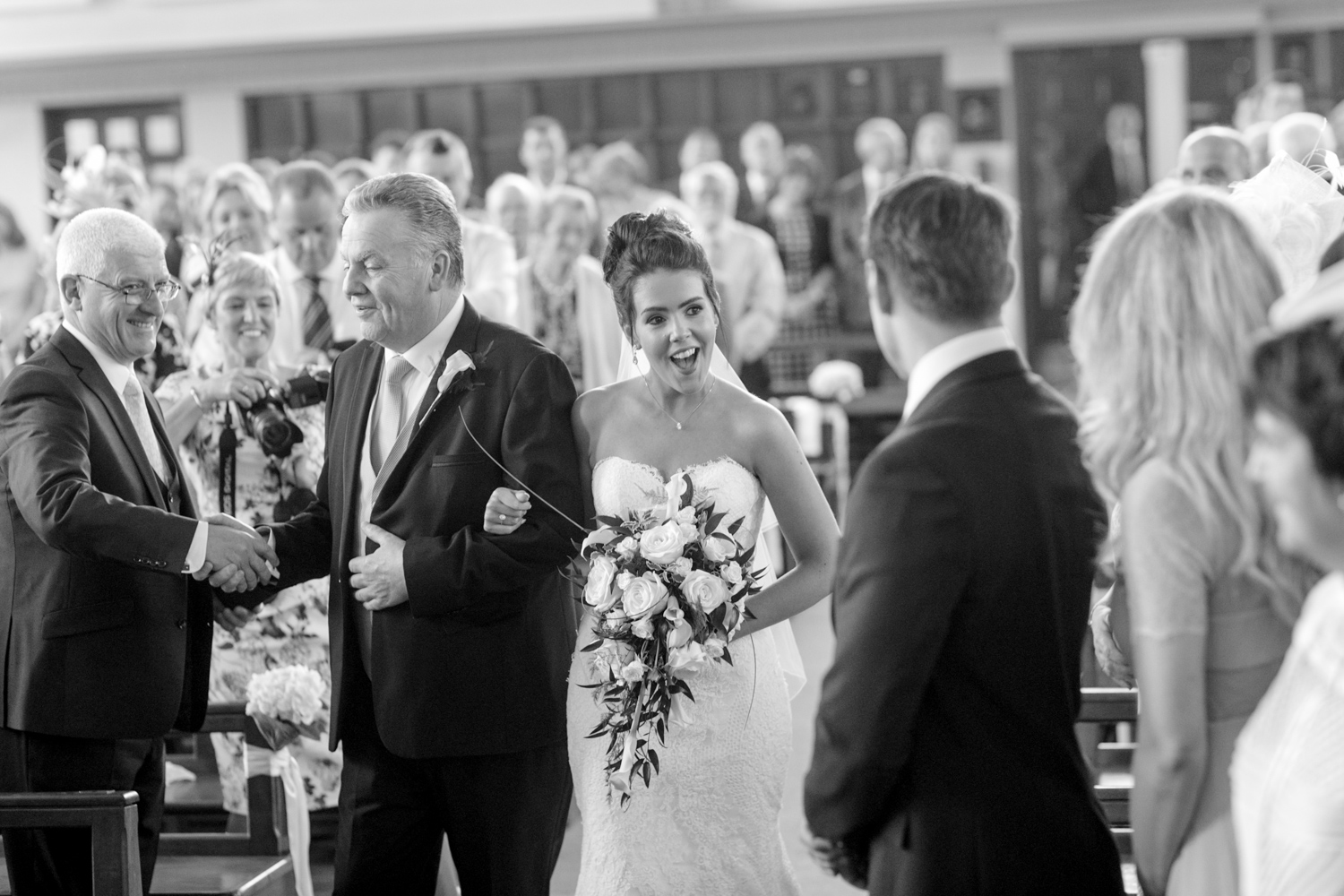 bride walks down the aisle with her did smiling at the guests