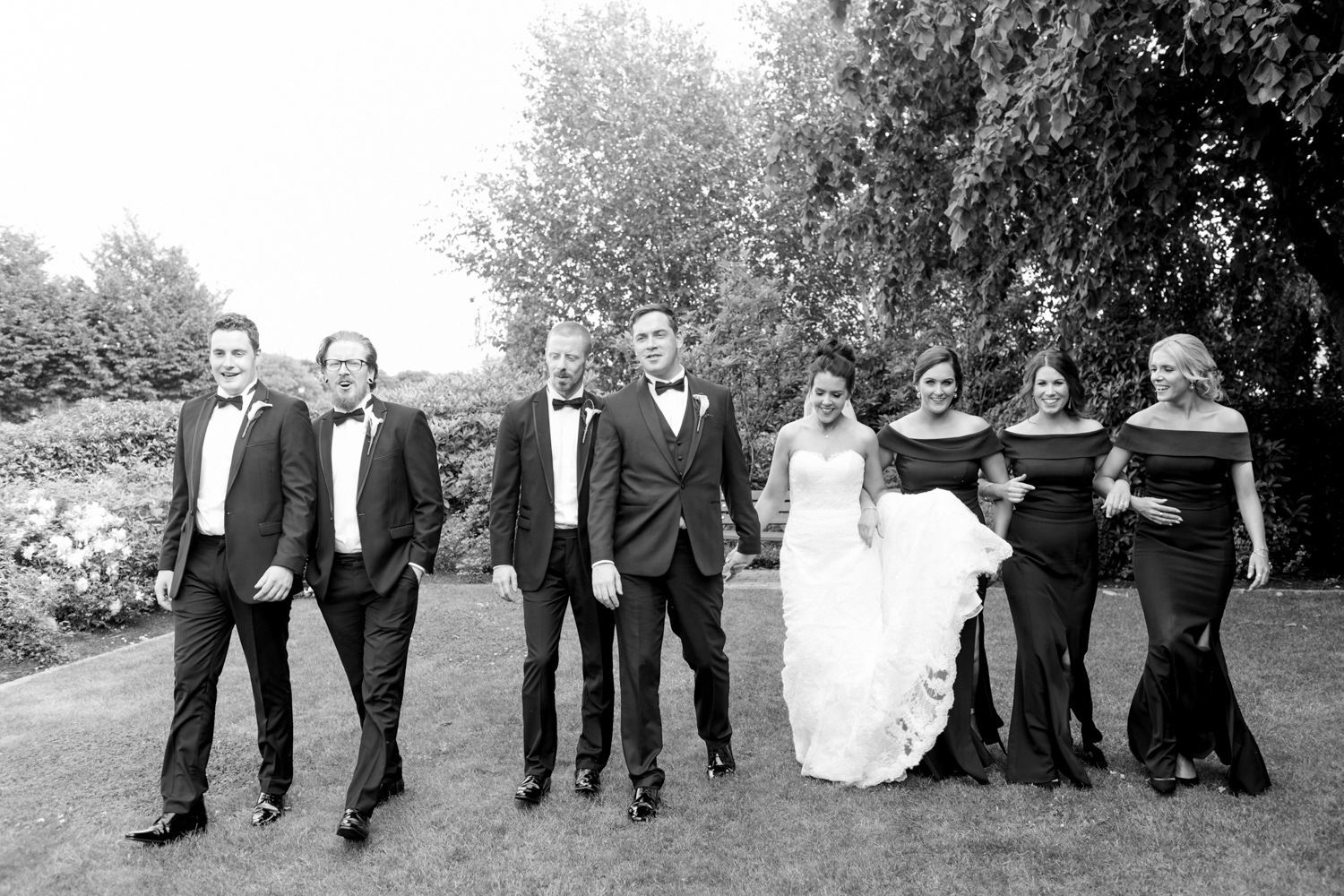 bride and groom with his groomsmen in black tux suits and bridesmaids in black long dresses