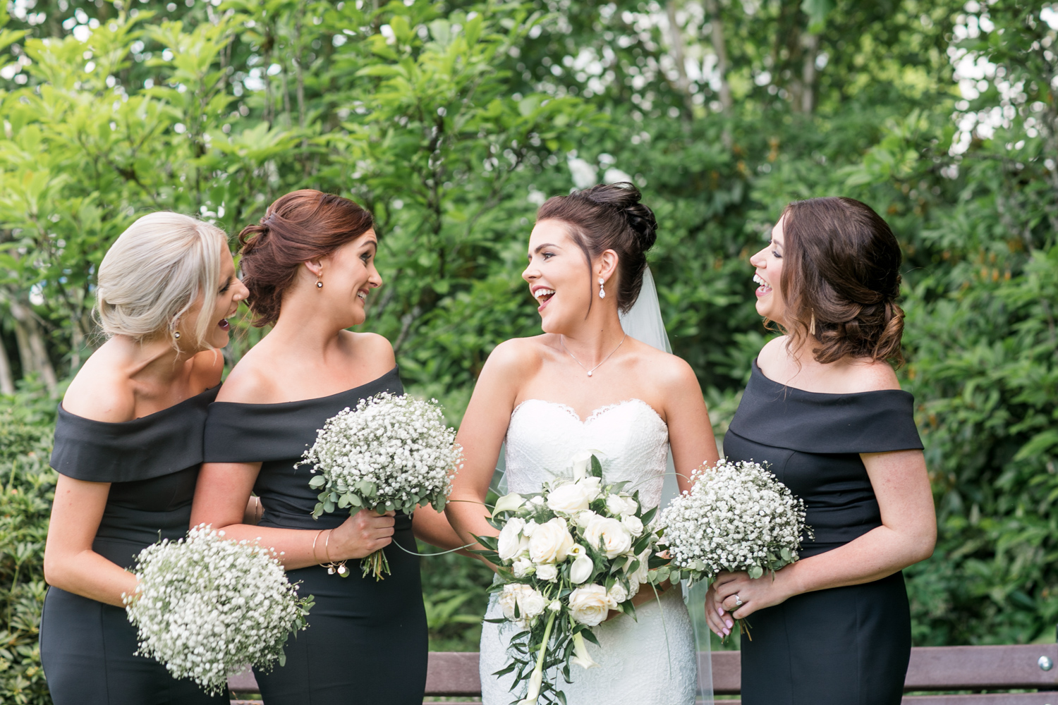 bride and bridesmaids smiling at each other holding the flowers in black dresses
