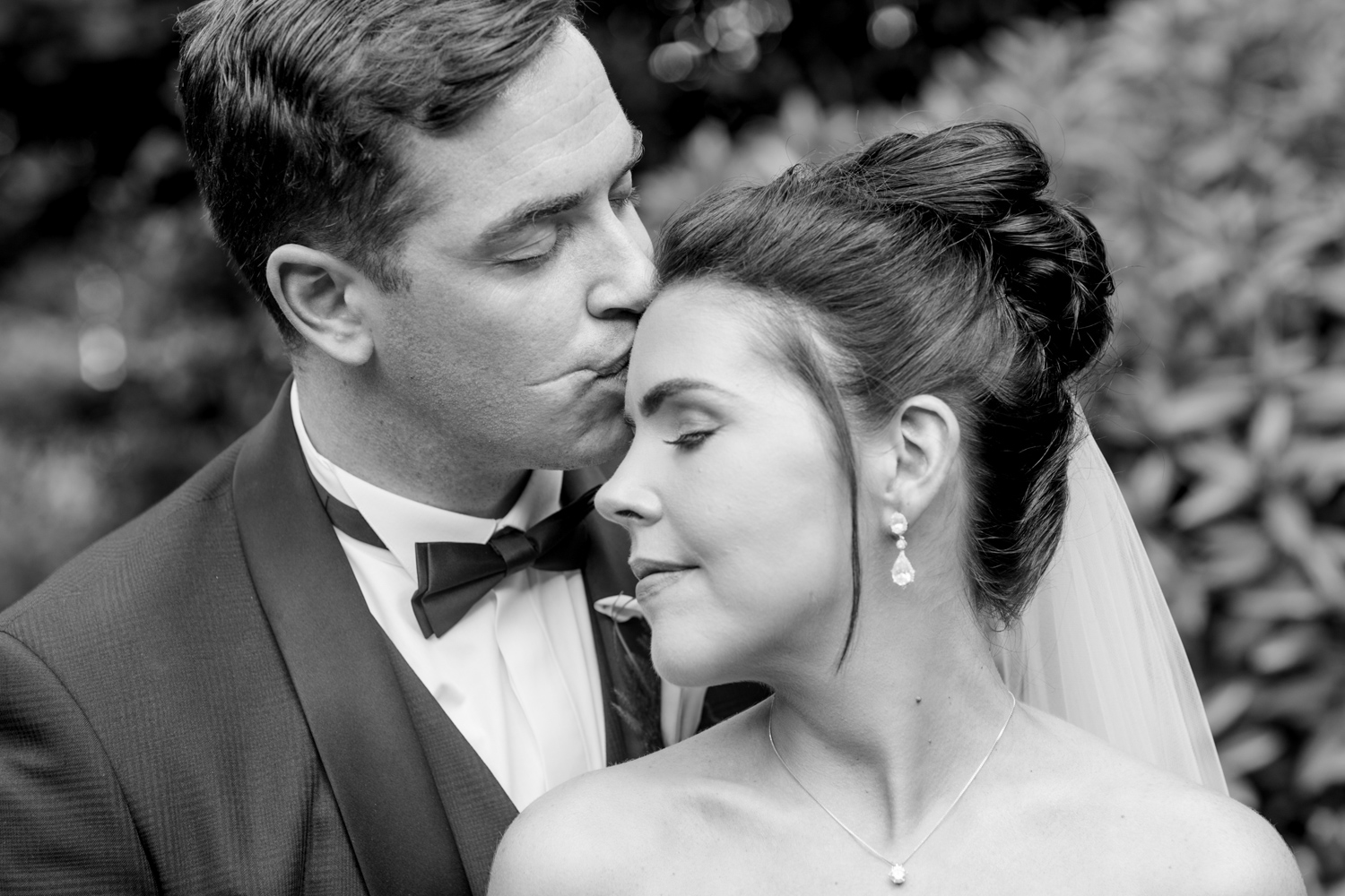 black and white photograph of groom kissing the forhead of the bride while her eyes are closed posing at slieve russell hotel in ireland