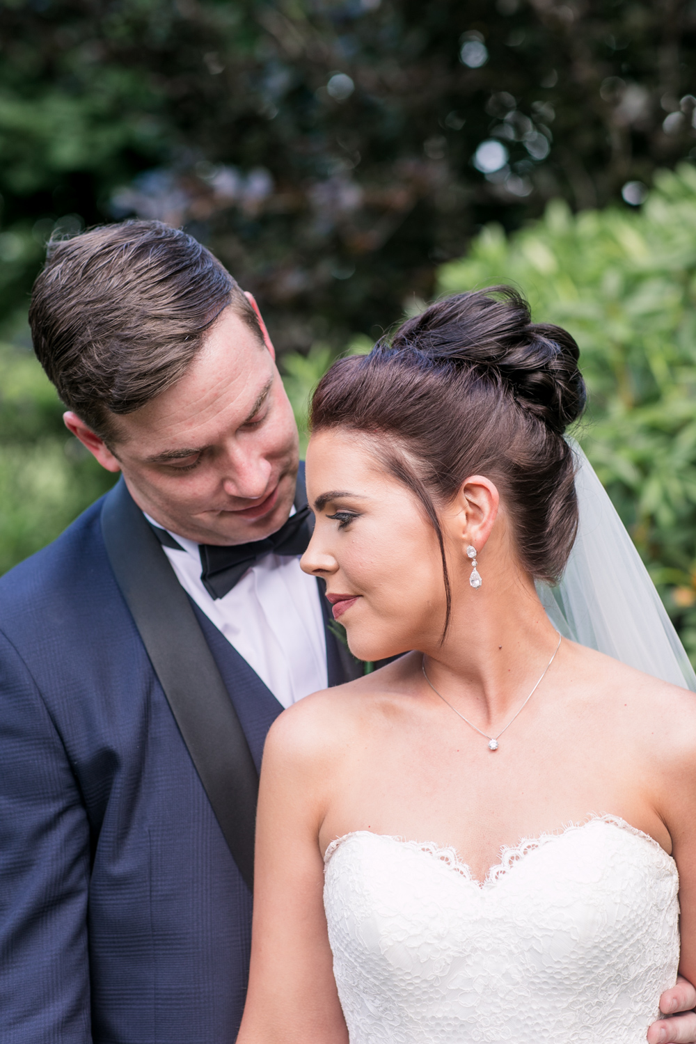 soft image of bride and groom at a black tie wedding posing on the grounds of slieve russell hotel in ireland