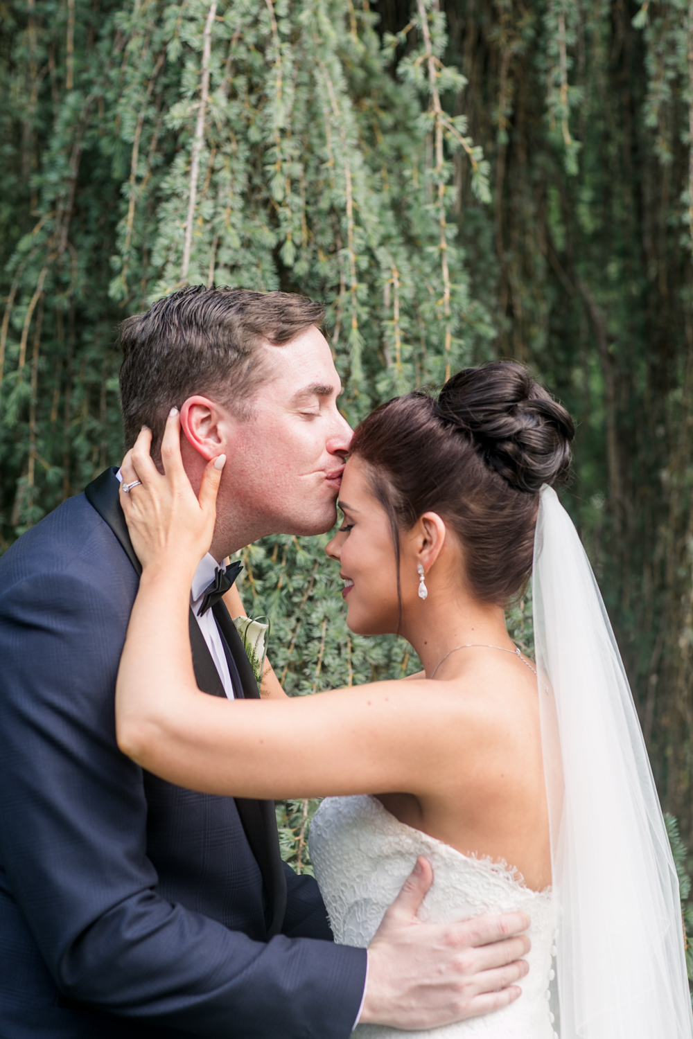 groom kissing the bride on the forhead while she is pulling him towards her at slieve russell hotel in ireland
