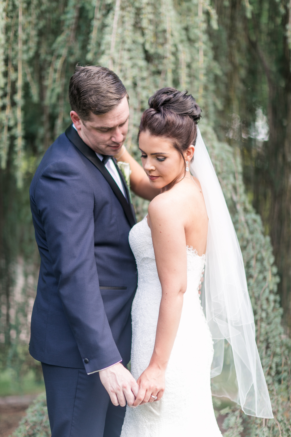 bride and groom holding hands with a willow tree in the background while both looking down posing on the grounds of slieve russell in ireland