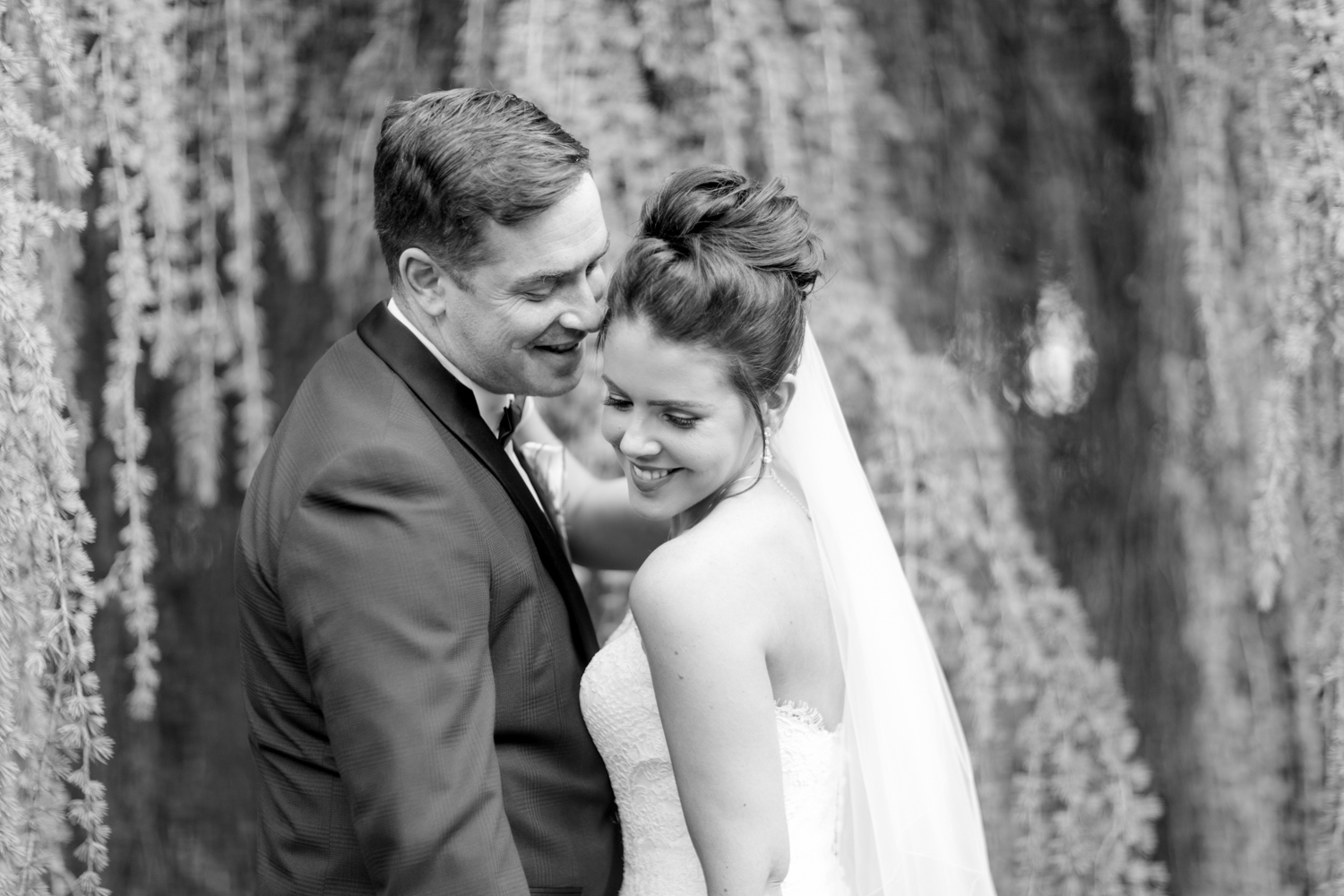 bride and groom with willow tree in the background bride laughing over her shoulder with groom looking right into her at slieve russell hotel in ireland