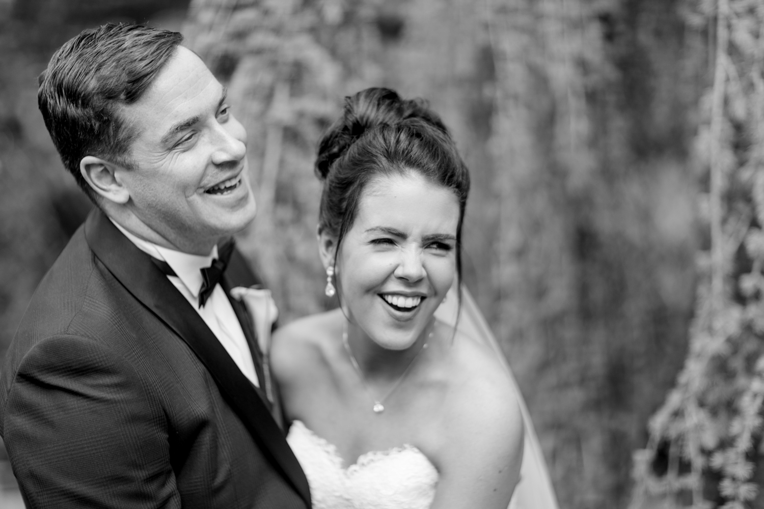 bride and groom energetically smiling into the camera groom wearing a black tux and bride wearing an off shoulder wedding dress