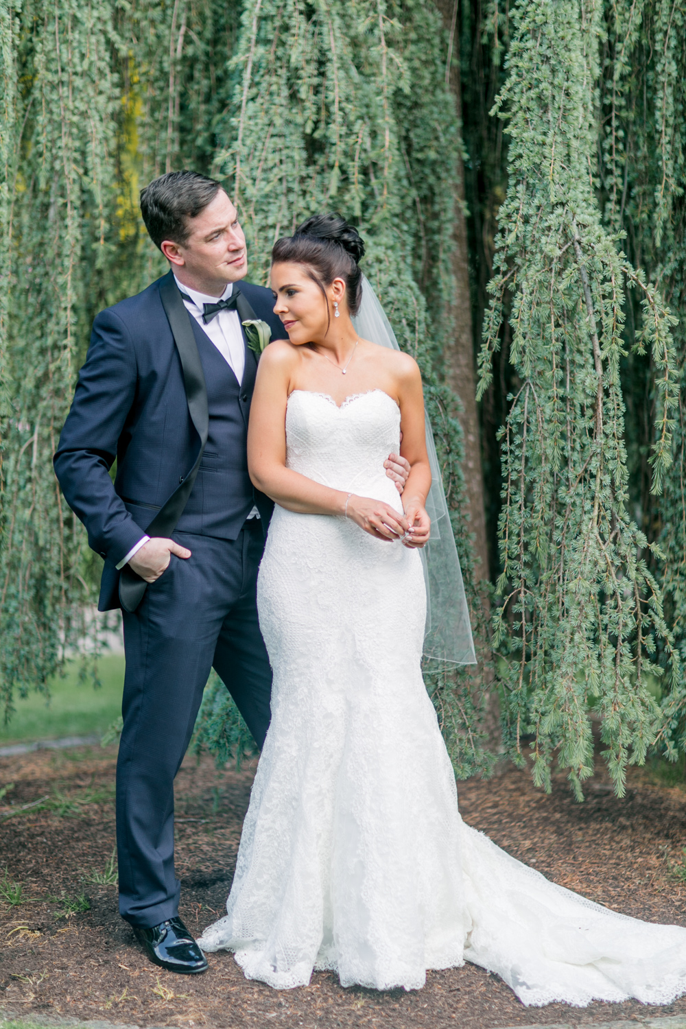 full length of brides open shoulder mermaid wedding dress and navy wedding tux with a willow tree in the background at slieve russell hotel