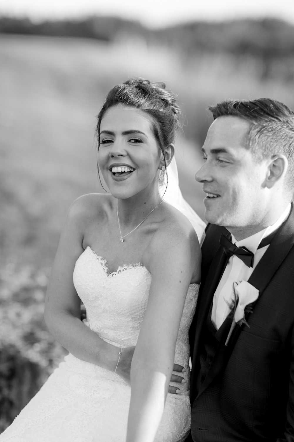 open shoulder wedding dress bride is laughing at the camera with a groom dressed in black tux at a wedding in ireland