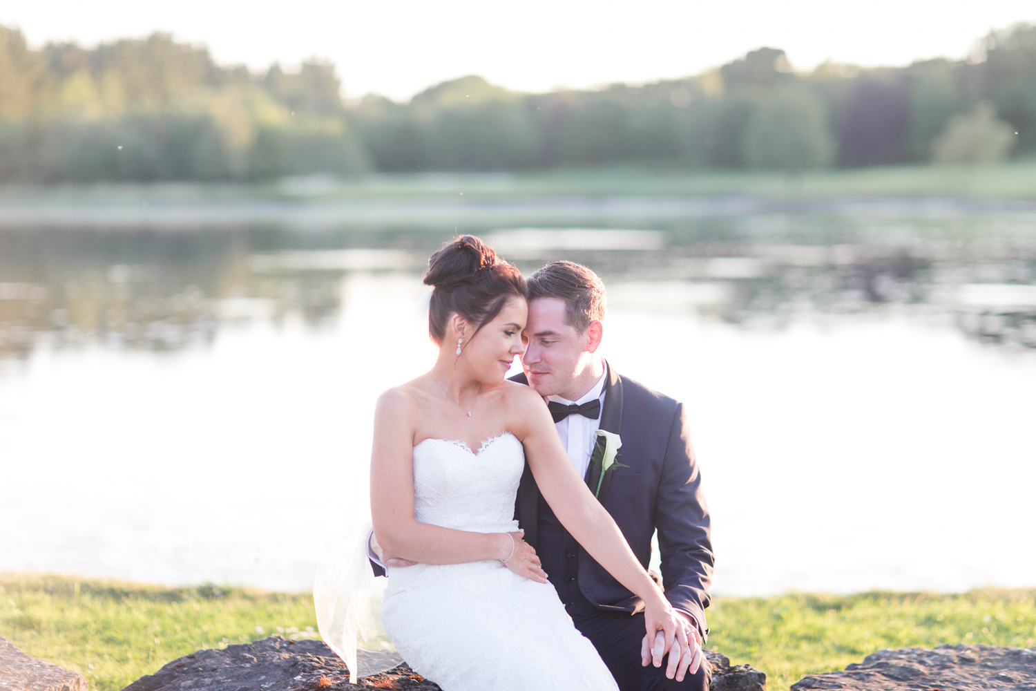 bride and groom posing for sun set photographs with lake in the background