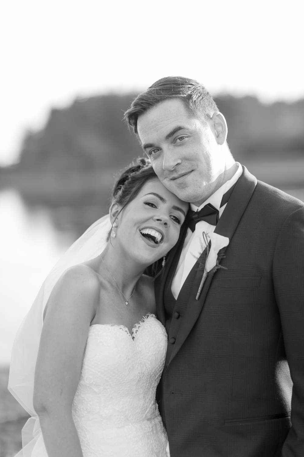 bride and groom laughing at the camera with a lake in the background