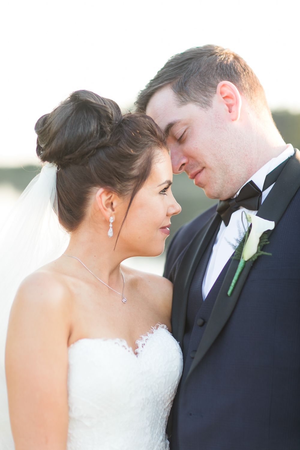 bride and groom portraits bride has a high bun and a long veil with open shoulder wedding dress